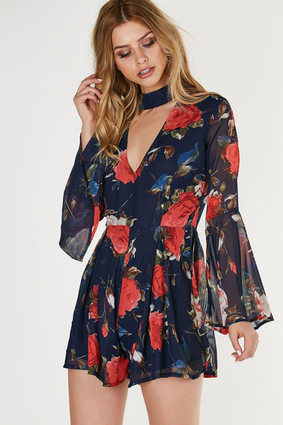 Flowy choker neck romper with bell sleeves and floral prints throughout. V-shape cut out in front and back with back zip closure.
