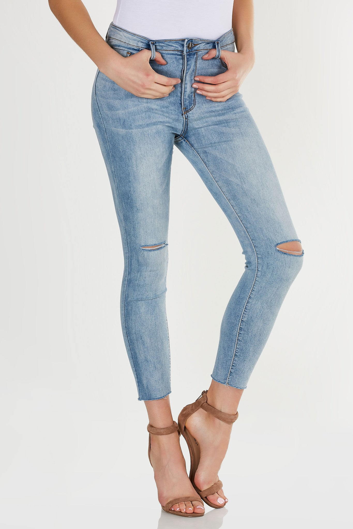 High waist raw hem five pocket skinny jeans with knee slits and button zipper closure at front.