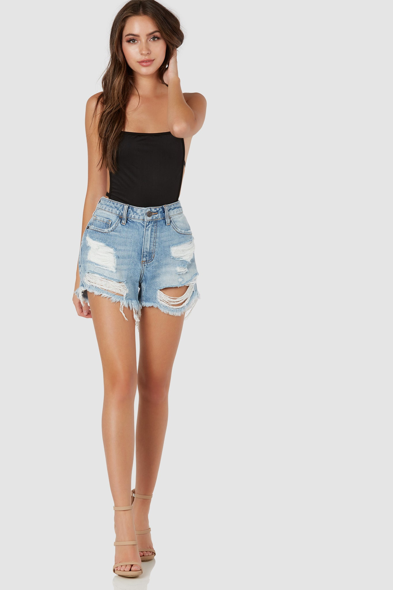 Casual mid rise denim cut-offs with trendy shredded detailing. Frayed raw hem finish with front zip closure.