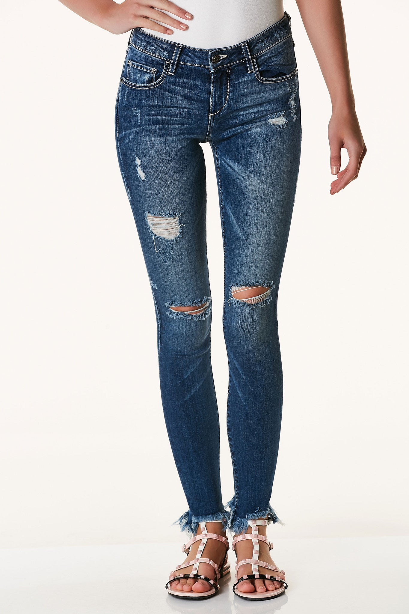 Basic skinny jeans with classic denim wash with slight vintage style fading. Distressing throughout with trendy frayed raw uneven hem.