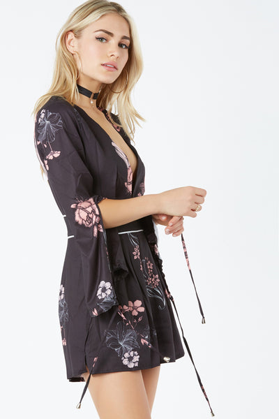 Chic long sleeve romper with deep V-neckline and cut out in back. Floral print throughout with slit detailing and ties for closure.
