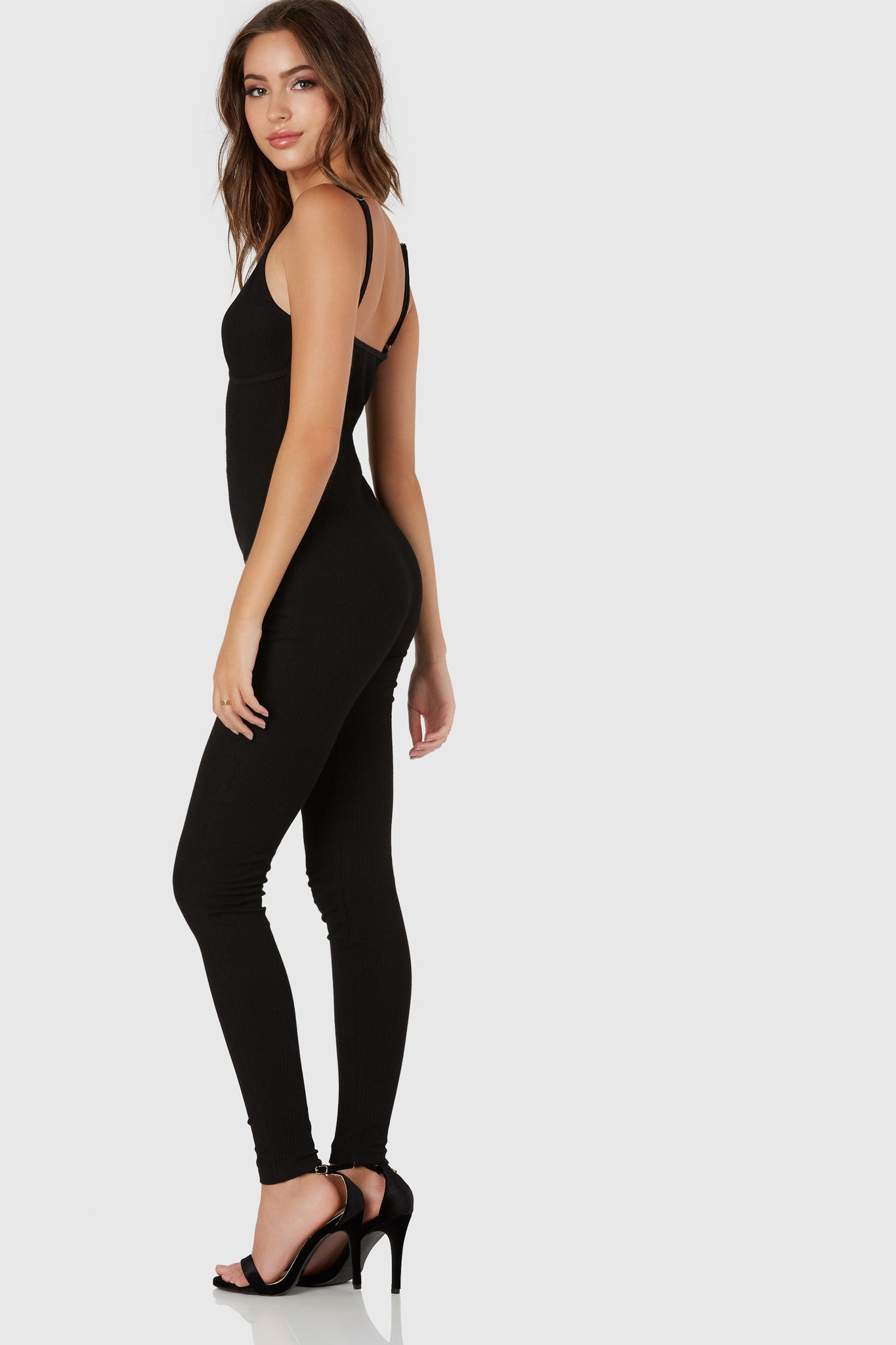 Sleeveless jumpsuit with plunging center slit. Ribbed throughout with hook and eye clasps for closure.