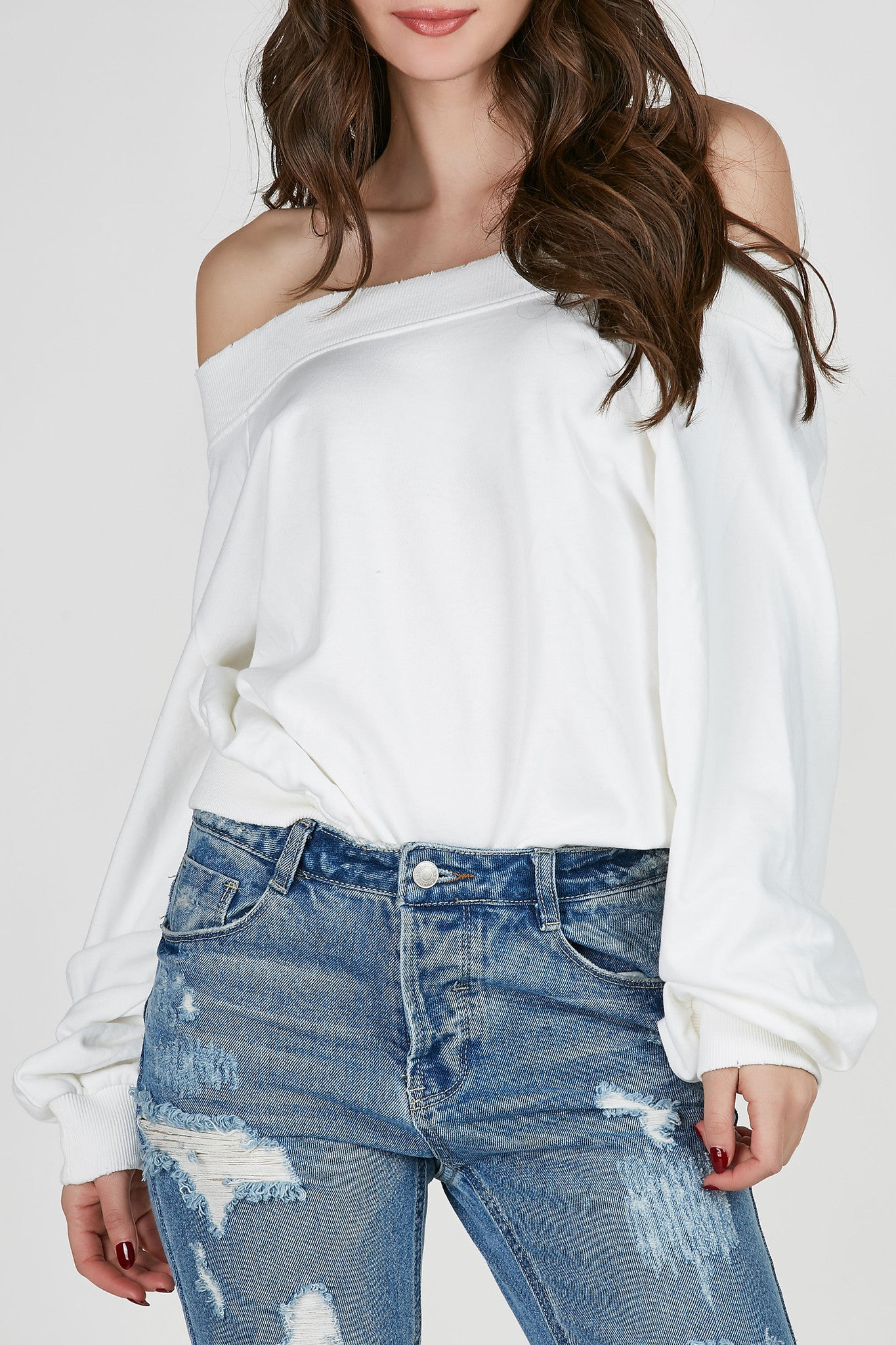 Ribbed off shoulder neckline with full length sleeves. Relaxed fit with subtle distressing at hem.