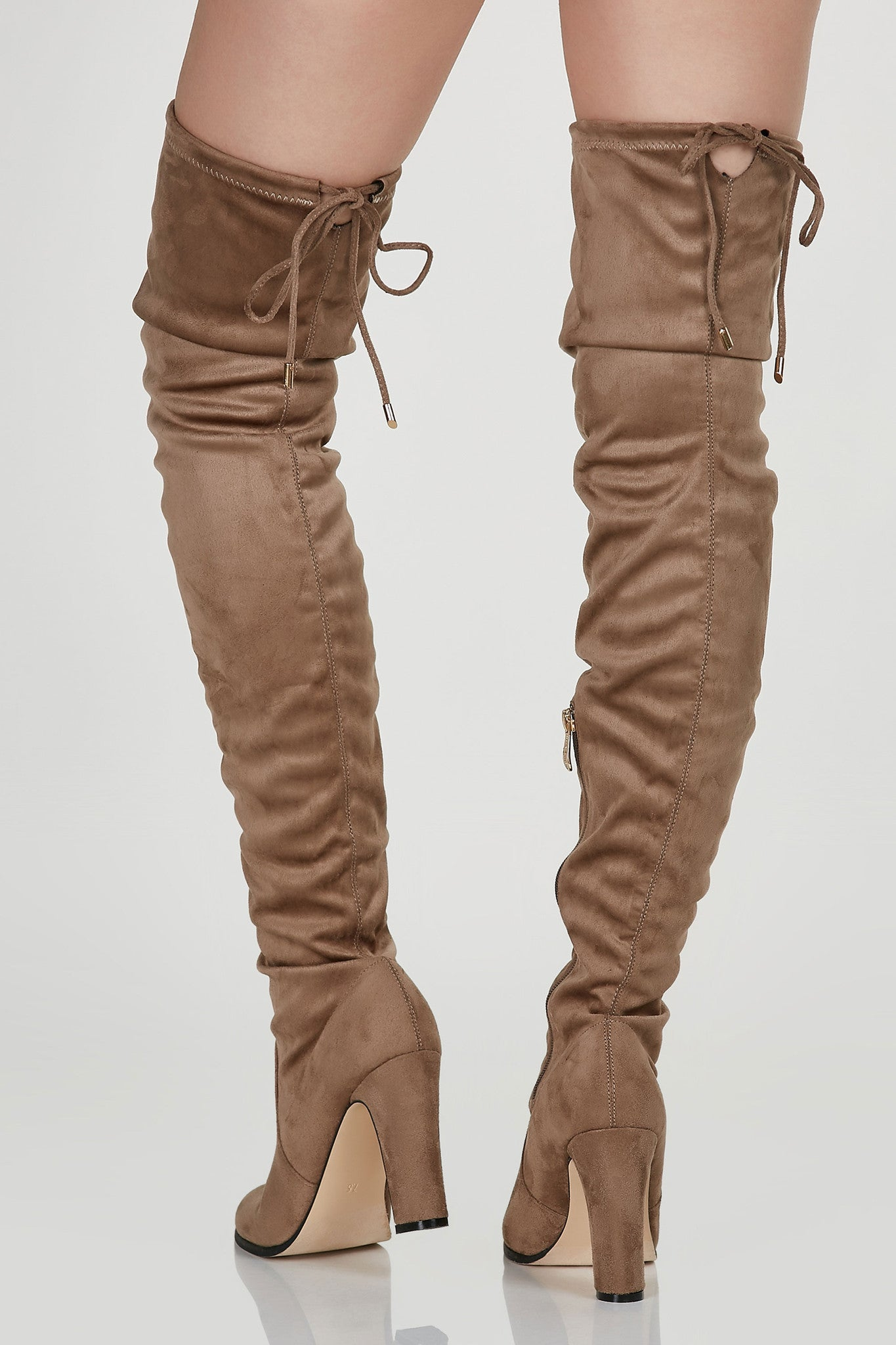 Slim fit thigh high boots with soft suede finish. Side zip closure with ties for fit at top.