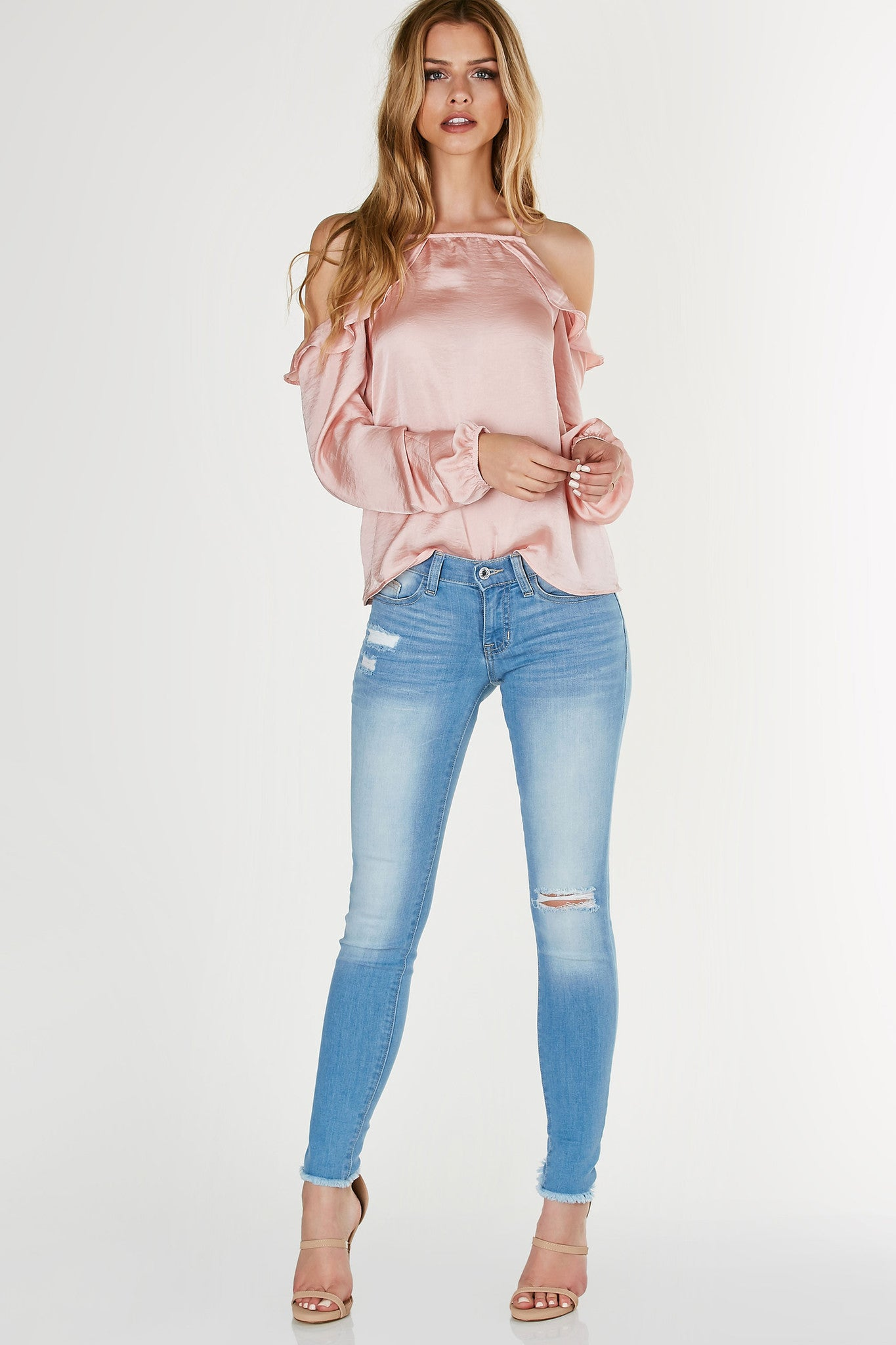 Classic light wash skinny jeans with comfortable low rise waist. Distressing in front with frayed raw hem finish.
