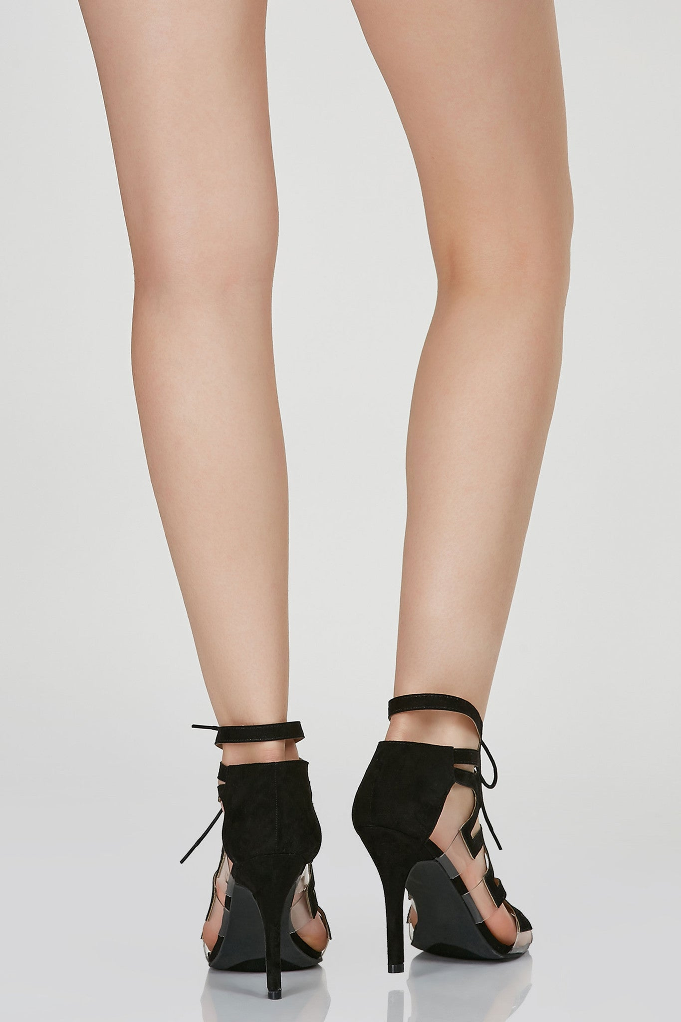 Cut out caged pumps with chic lace up closure. Clear panels at sides with peep toe and suede finish.