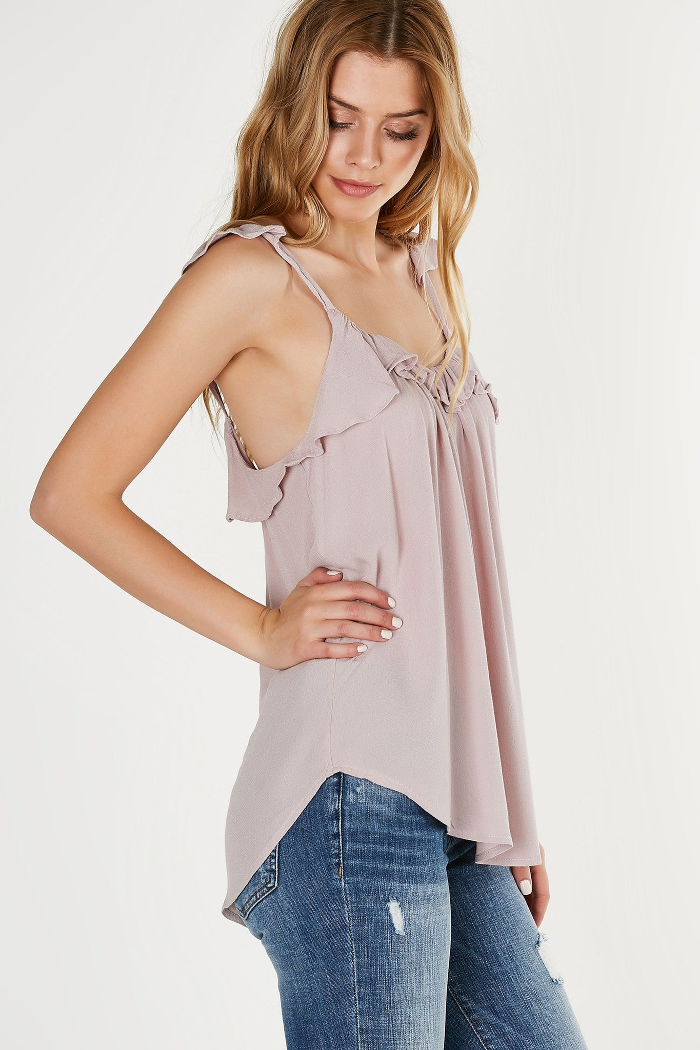 Flirty sleeveless top made of lightweight material with flowy fit. Ruffle detailing throughout neckline and shoulder straps.