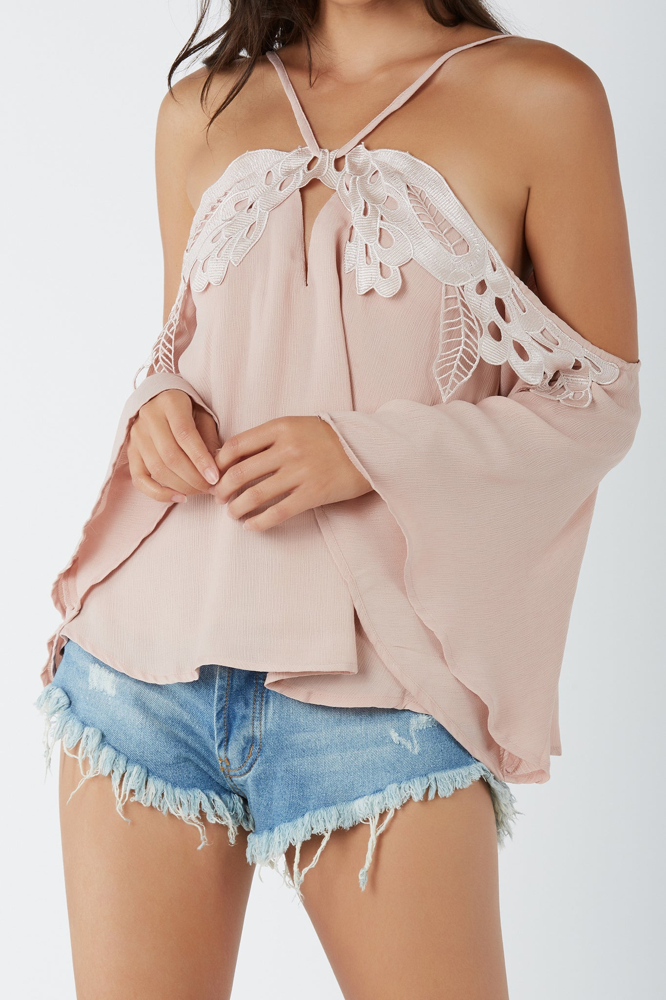 Chic cold shoulder top with bold crochet patch detailing. Halter style straps with drawstring tie finish in back.