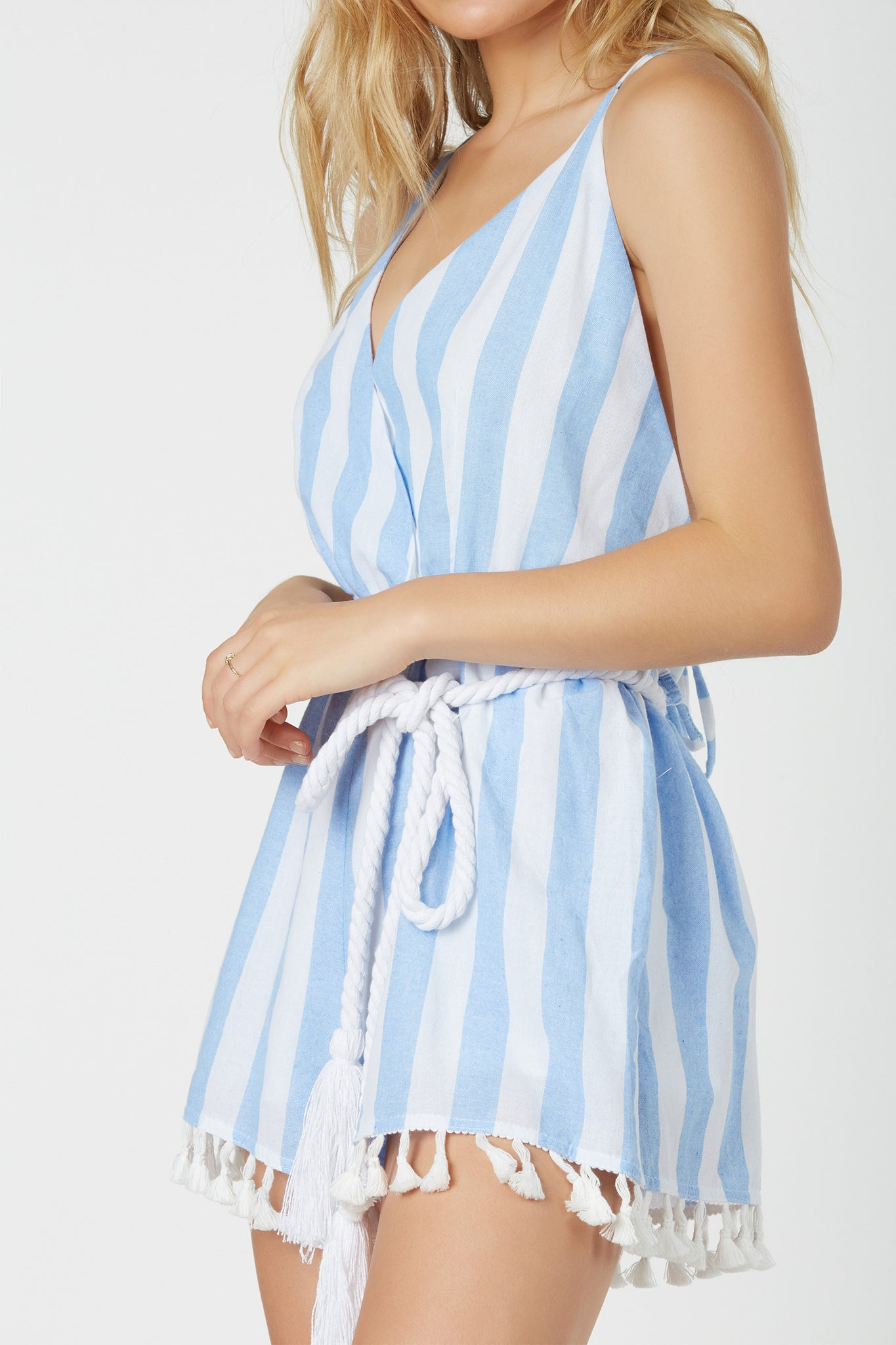 Playful spaghetti strap romper with overlap V-neckline. Stripe patterns throughout with fun tassels at hem and roped waist tie for added detail.