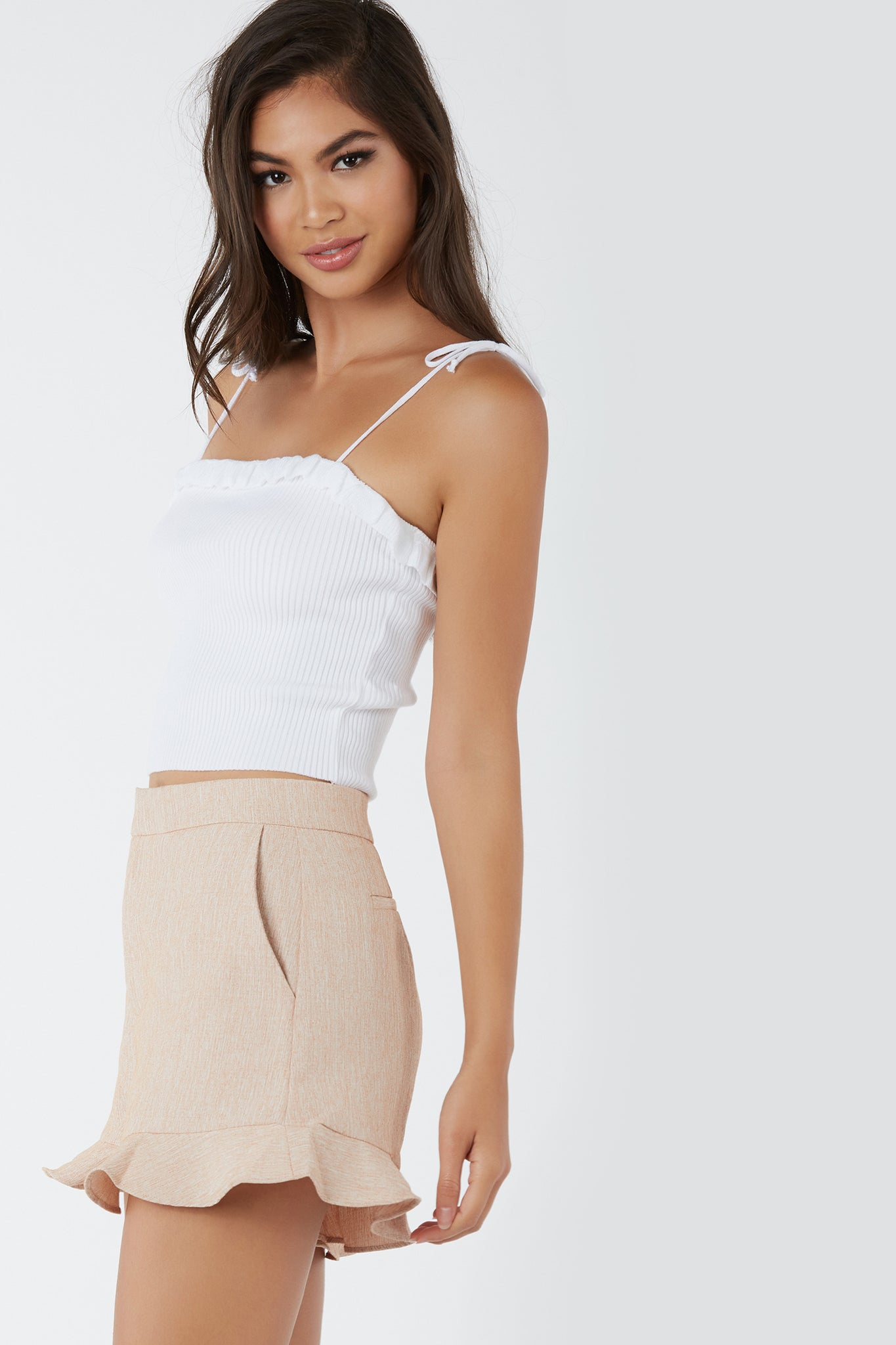 Flirty ribbed crop top with adorable ruffle trim detailing. Comfortable fit with amazing stretch and trendy tie up shoulder straps.