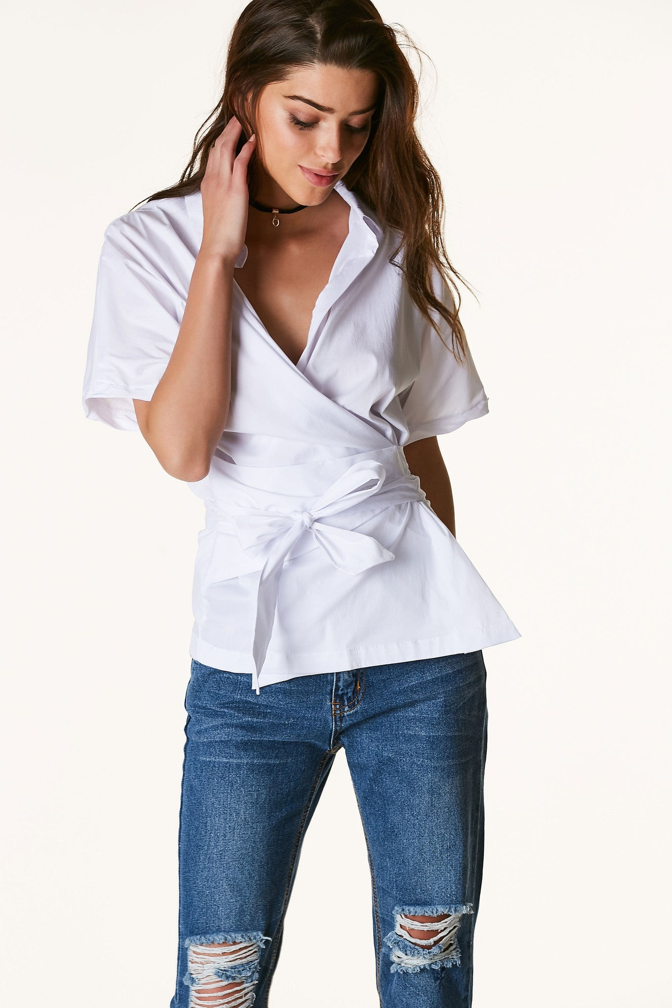 Wrap over short sleeve blouse with comfortable relaxed fit. Crisp collar with cut out in back and ties in front for closure.