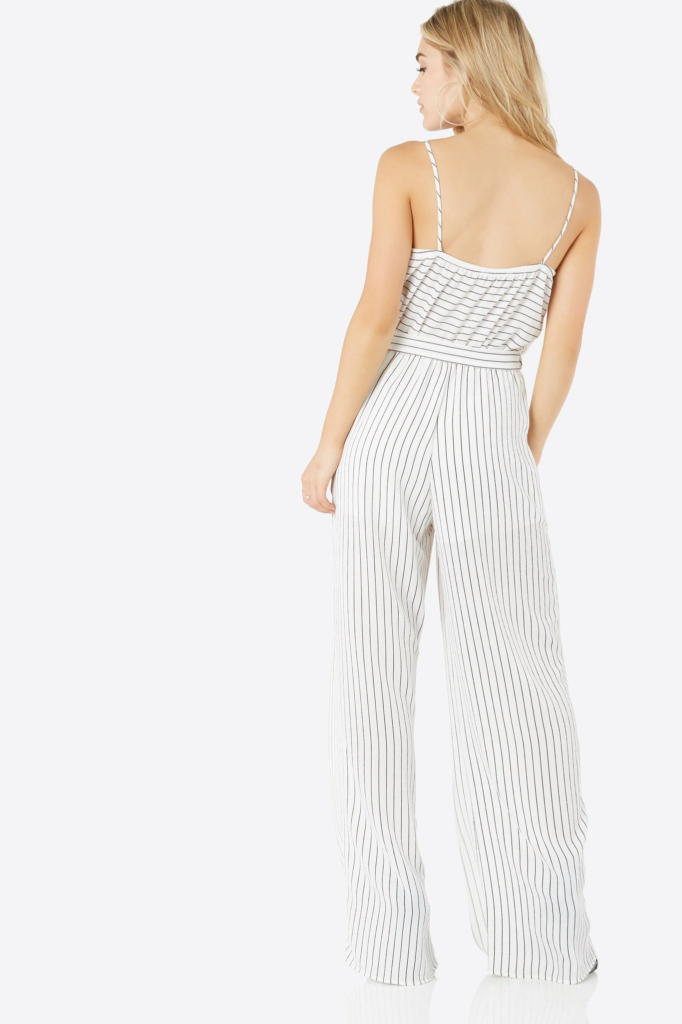 Sleeveless jumpsuit with stripe print throughout. Deep V-neckline with waist tie detailing and wide leg fit.