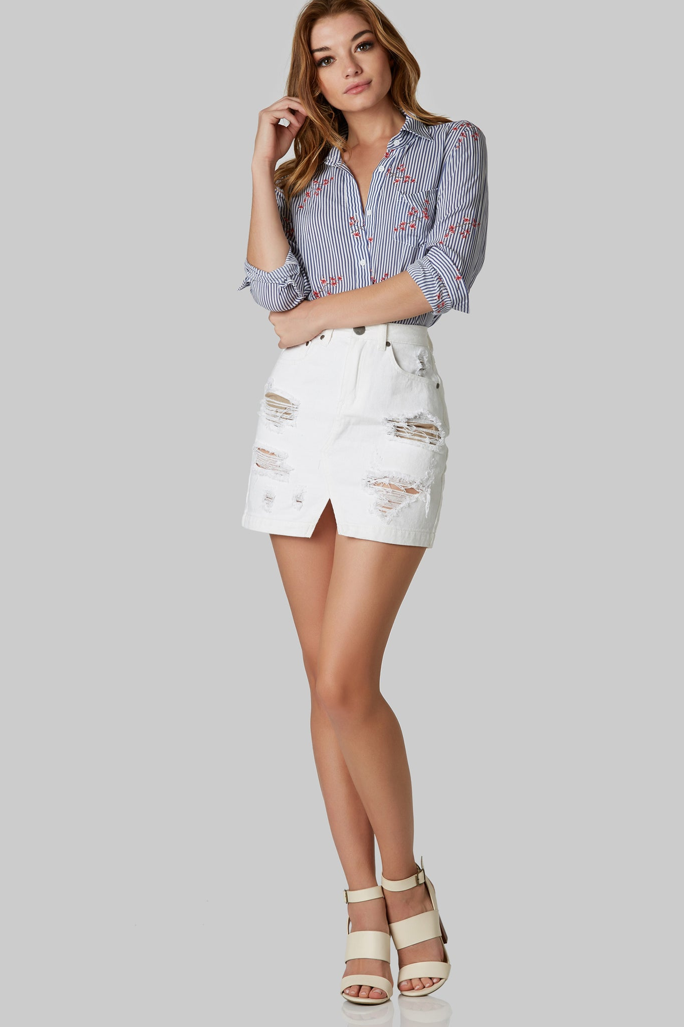 High rise denim mini skirt with shredded detailing throughout. 5 pocket design with cut out hem and button zip closure.