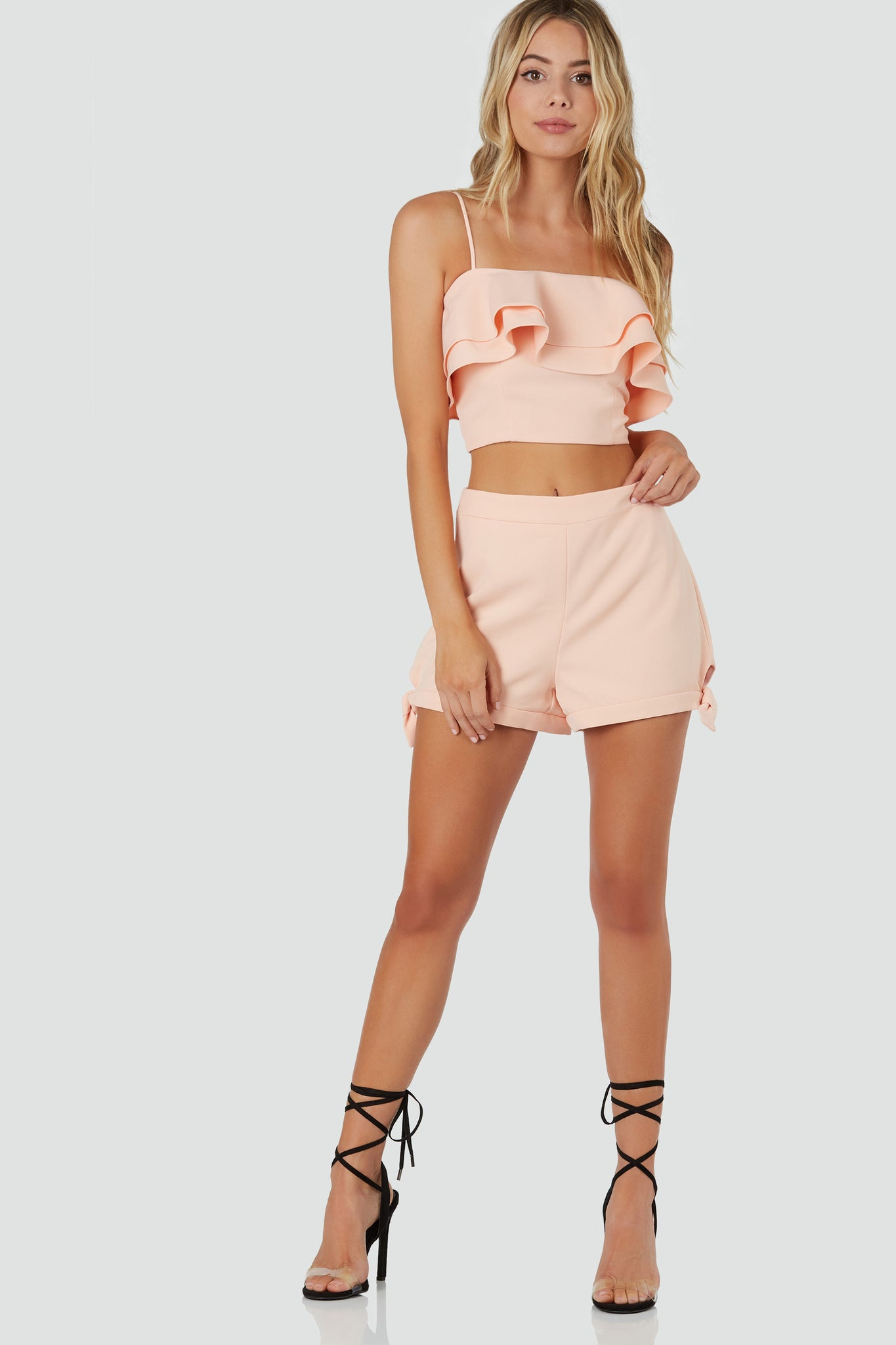 Flirty spaghetti strap top with tiered ruffle design and cropped hem finish.