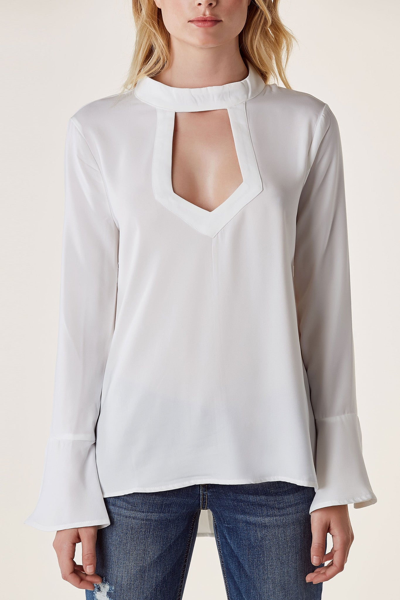 Chic high neck blouse with cut out in front and back. Longline hem with flirty bell sleeves and button closure in back.