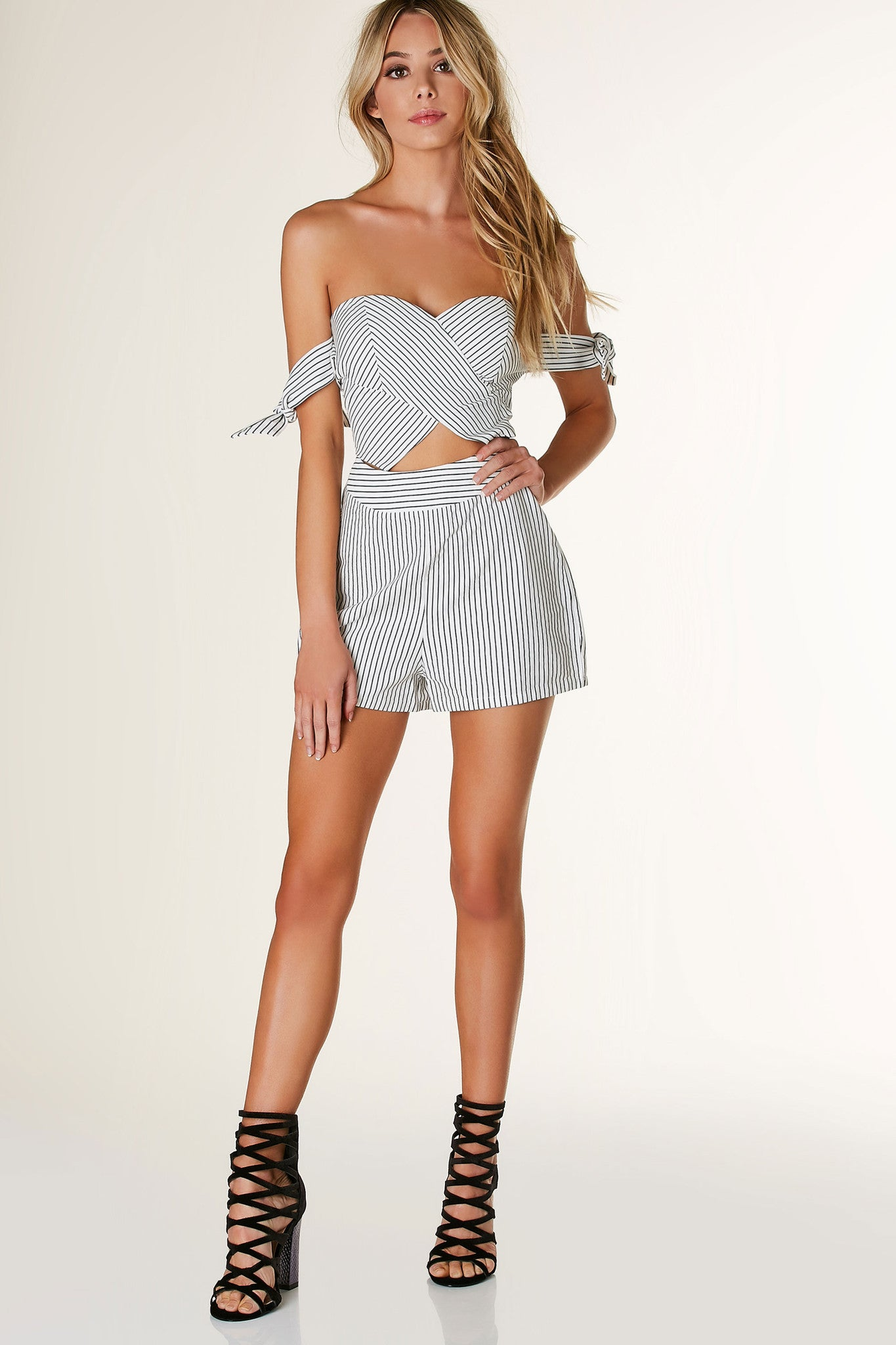 Flirty sweetheart neckline romper with tie up sleeves and center cut out. Pinstripe patterns throughout with back zip closure.