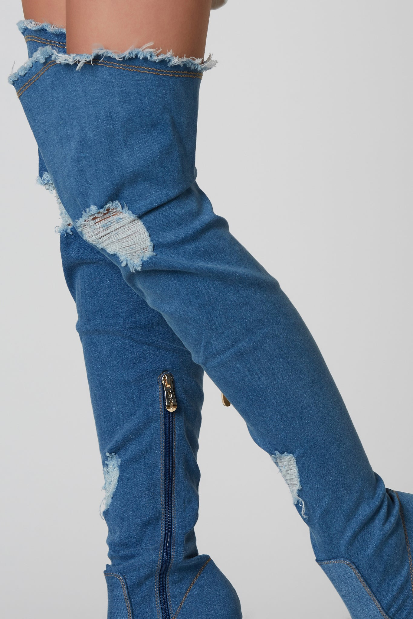 Sassy denim thigh highs with raw hem finish and distressed detailing. Peep toe finish with side zip closure.