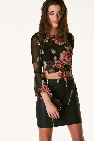 Rose printed mesh crop top with long bell sleeves and knotted hem finish. Rounded neckline with keyhold cut out and button closure in back.