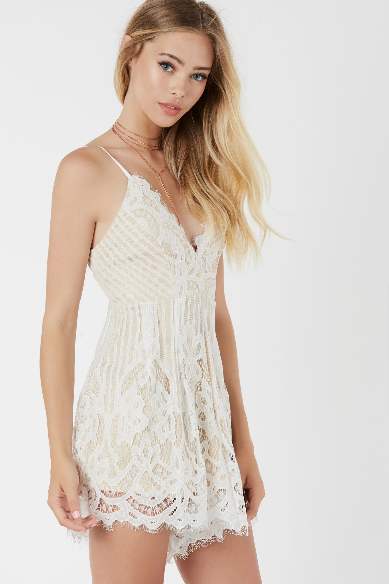 Delicate spaghetti strap romper with nude lining and lace overlay. Eyelash trim detailing with lace up design in back.