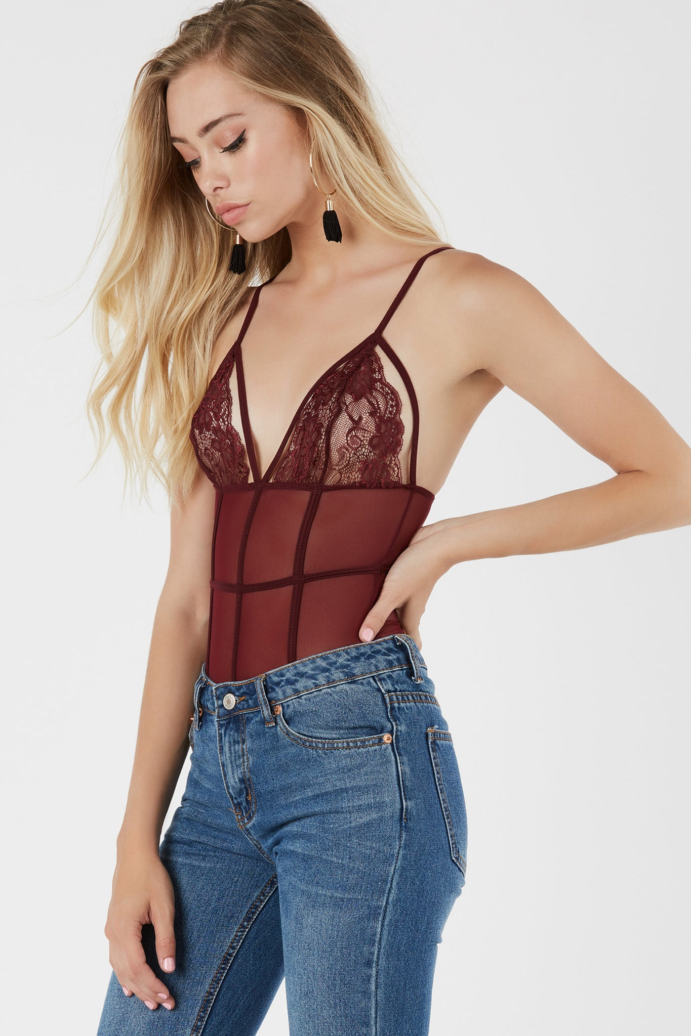 Sultry mesh bodysuit with caged design and contrast lace detailing.