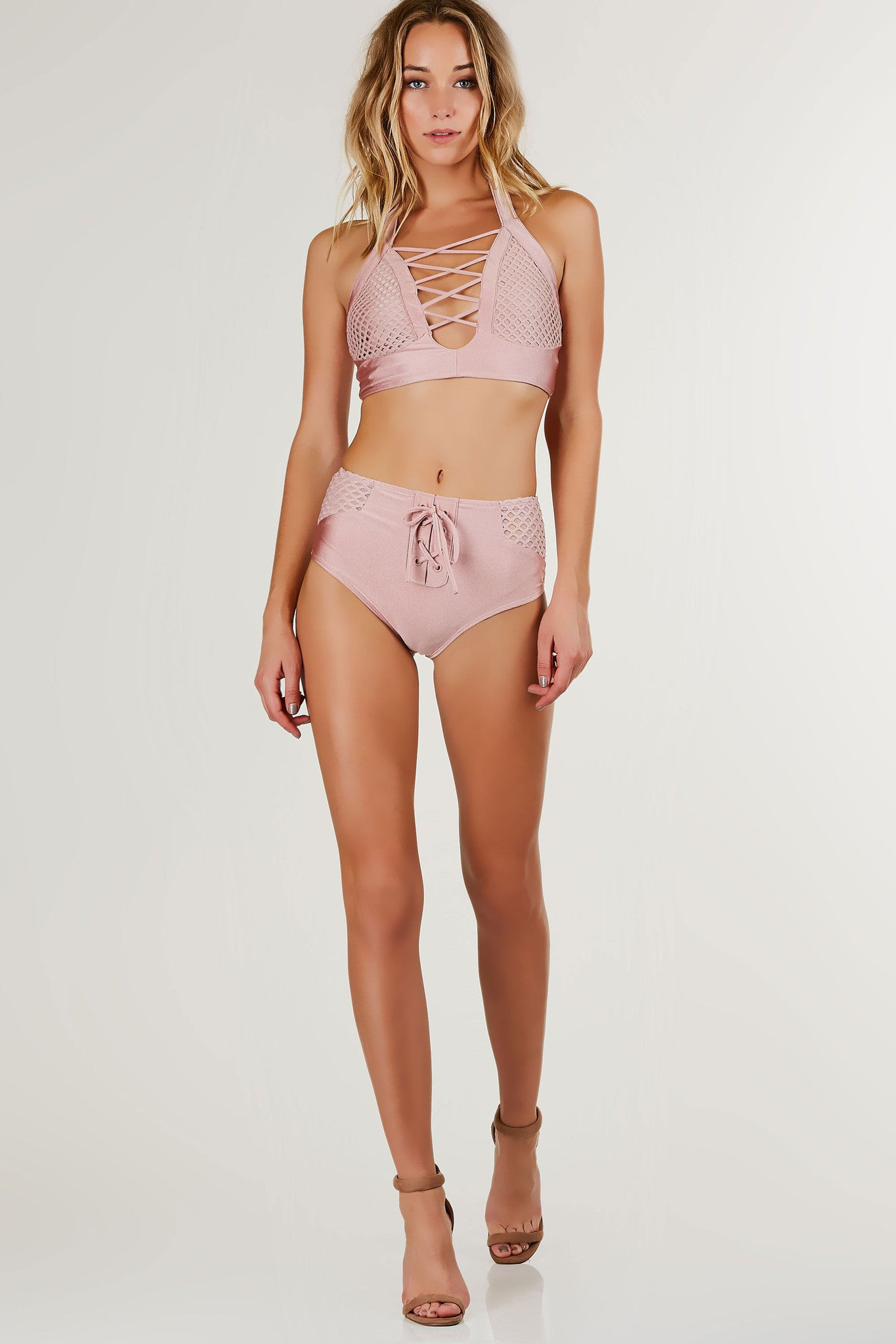 Stay breezy in the Lace Up Mesh Bikini that features a slip-on, low plunging halter, mesh panels, and faux lace up detailing. The bottoms feature a slip-on, high waisted, high cheeky cut, and front lace up detailing.
