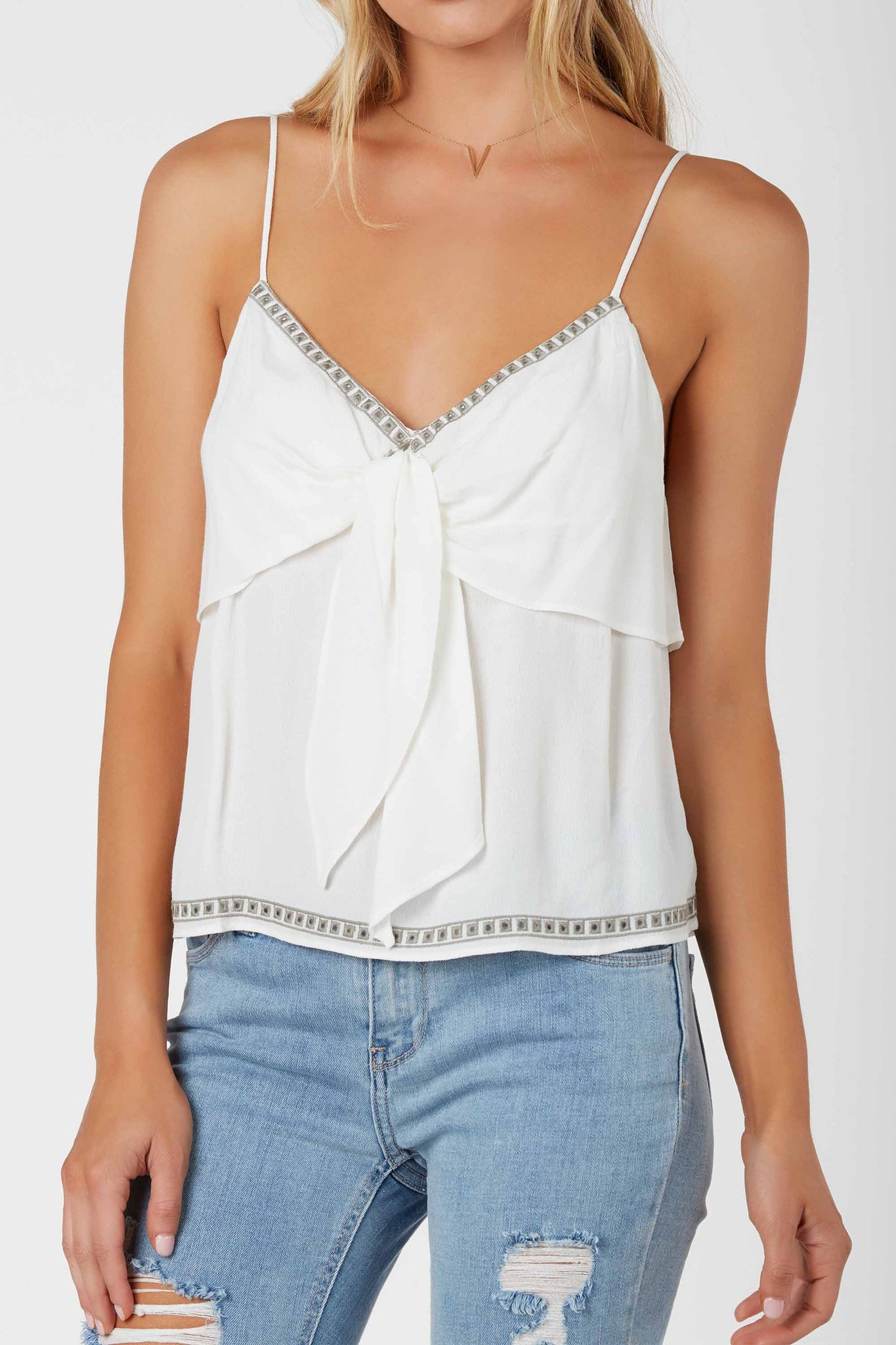 Lightweight spaghetti strap cami with V-neckline and tiered design. Front tie and embroidered trim detailing.