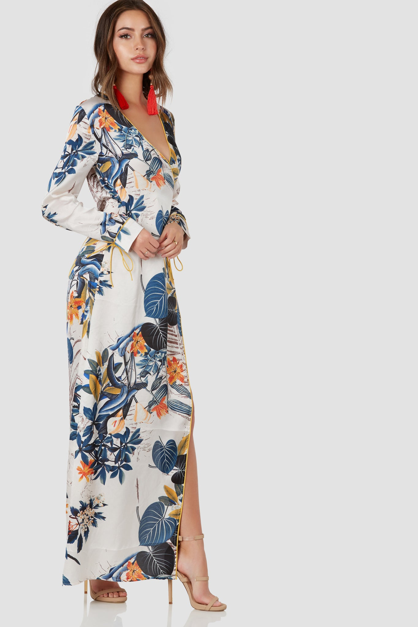 Stunning maxi dress with wrap design and botanical print throughout. Smooth satin-like finish with contrast piping and front tie closure.
