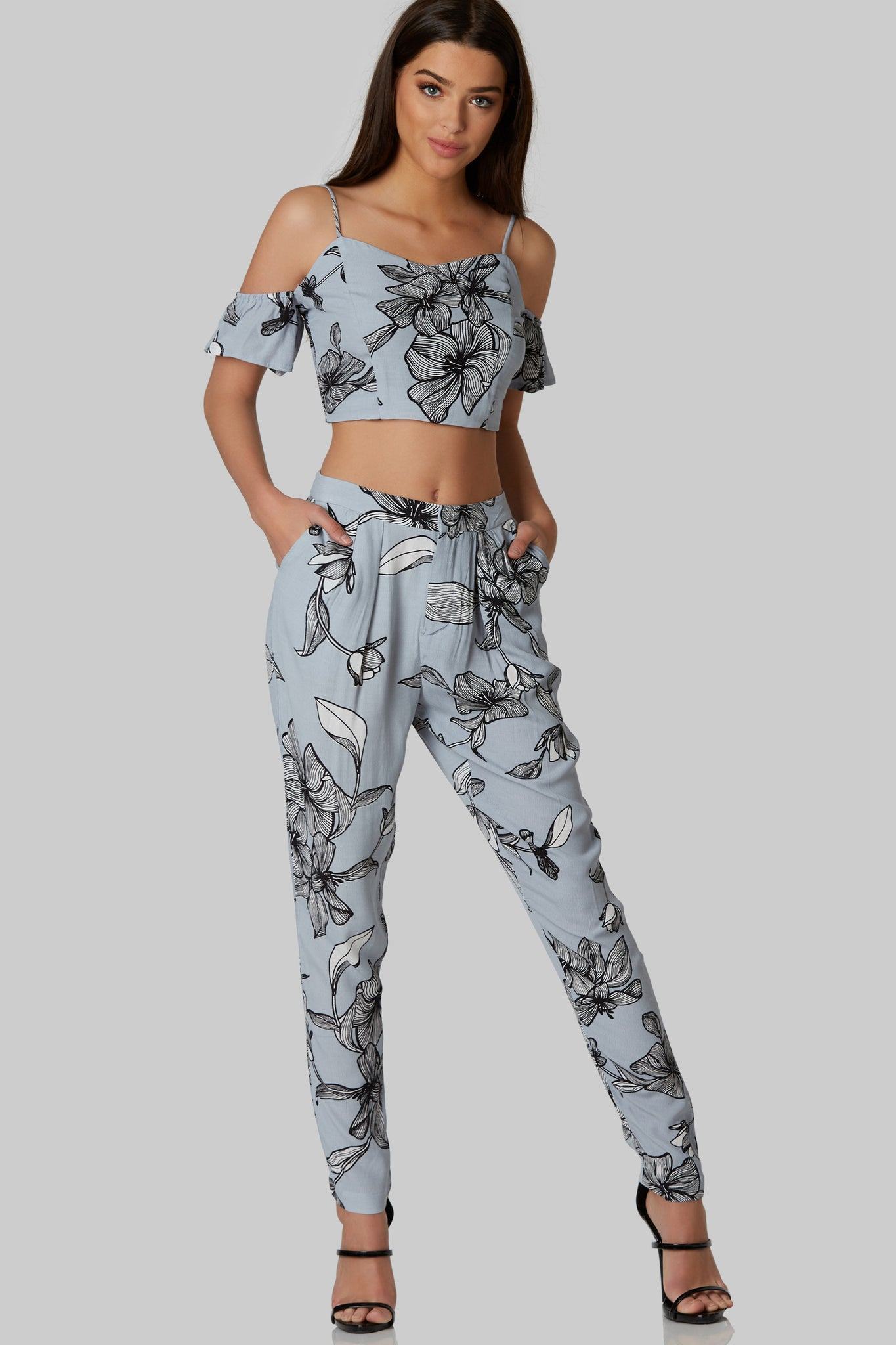 Chic cold shoulder crop top with floral patterns throughout. Fully lined with back zip closure. Comes in a set with matching bottoms sold separately.