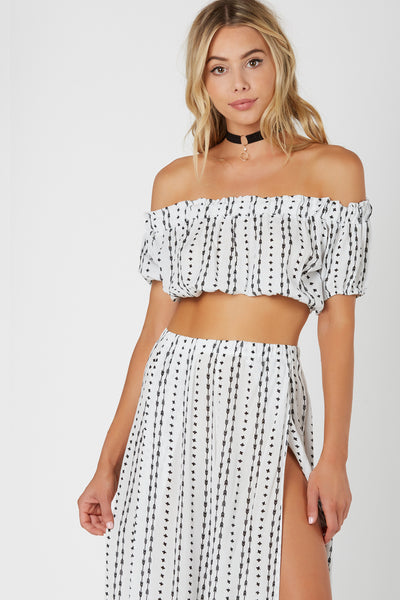 Flirty off shoulder top with dainty patterns printed throughout. Cropped hem with elasticized band