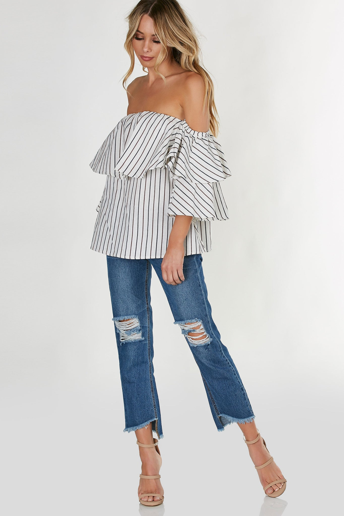 Flared off shoulder top with tiered ruffle sleeves and stripe patterns throughout. Structured fit with elasticized neckline.