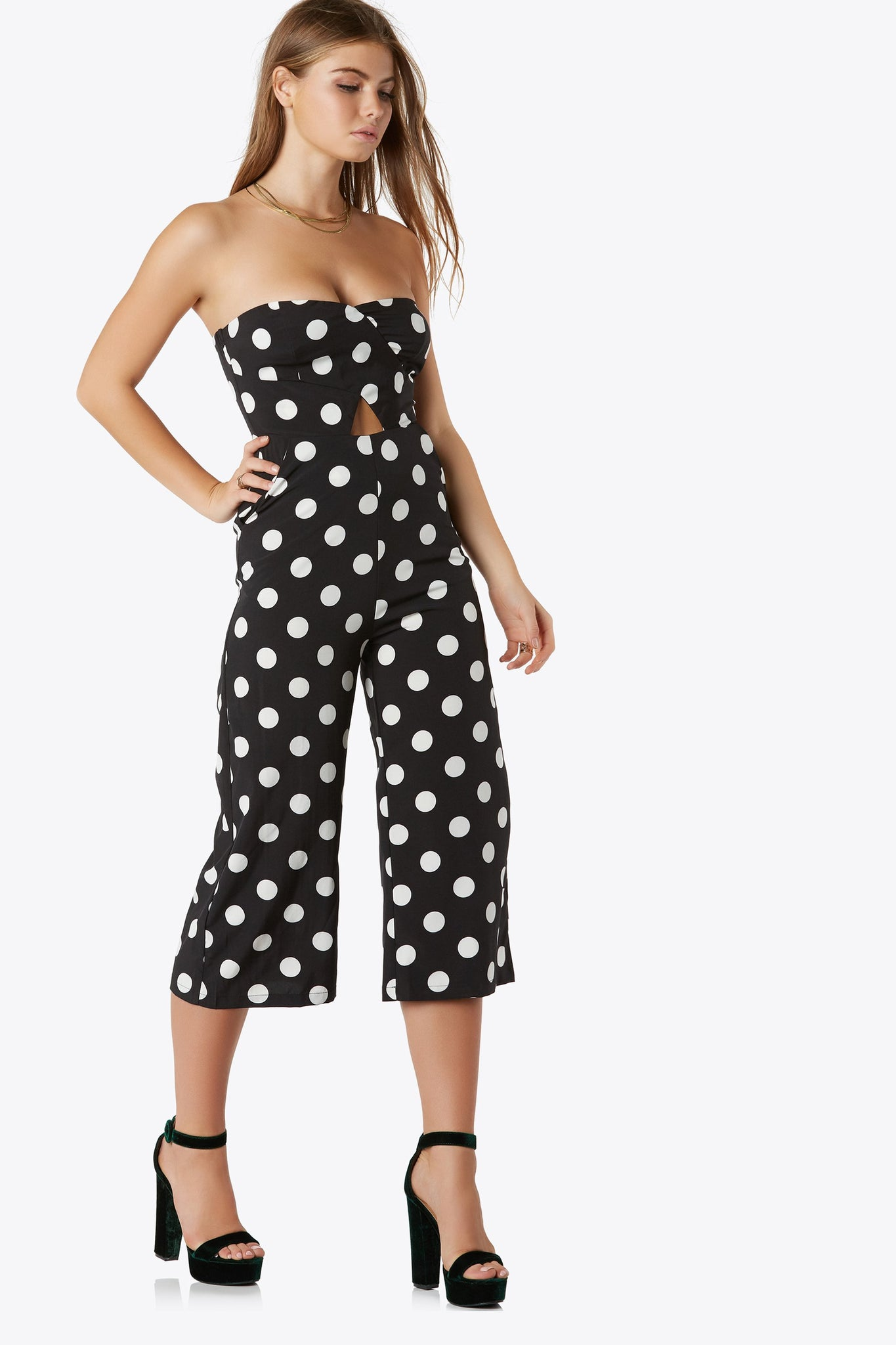 Flowy strapless jumpsuit in polka dot print. Features front hidden pockets, triangular cut out and back hidden zipper and hook closure. Sleek inside rubber lining around neckline for additive support.