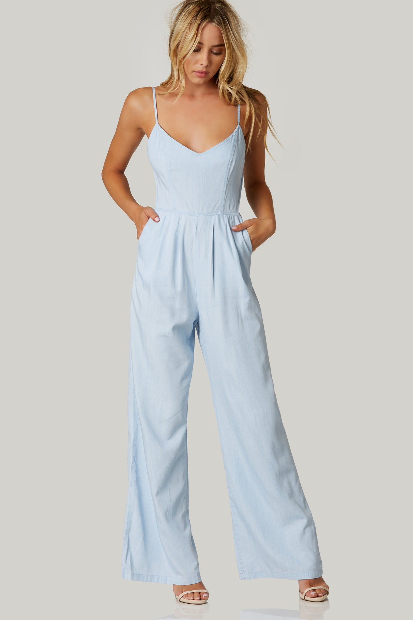 V-neck sleeveless jumpsuit with adjustable shoulder straps and wide leg fit. Open back with tie and zip closure.