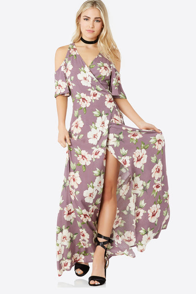Flowy cold shoulder maxi dress with deep V-neckline and wrap front design. Floral print throughout with waist tie for closure.