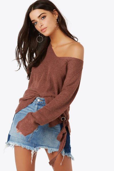 Edge meets comfy with the relaxed fit v-neck rib knit top. Metal loops and adjustable knit tie accents on hem. Center slit in back for added detail.