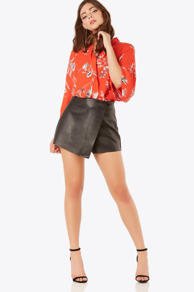Faux leather wrap skort with hidden side zip closure. Comfortable fit with asymmetrical hem finish.