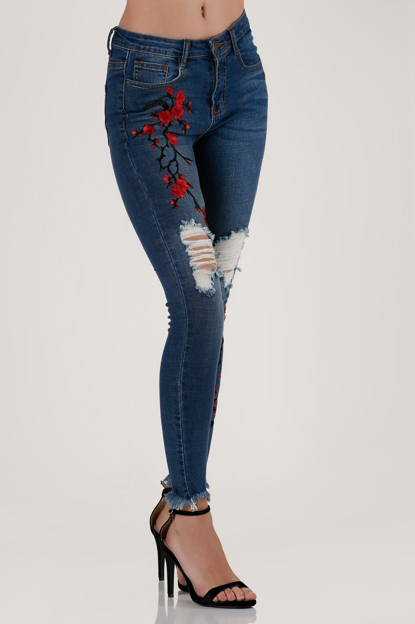 High rise skinnies with cherry blossom embroidery in front. Frayed uneven raw hem finish with 5 pocket design and button zip closure.