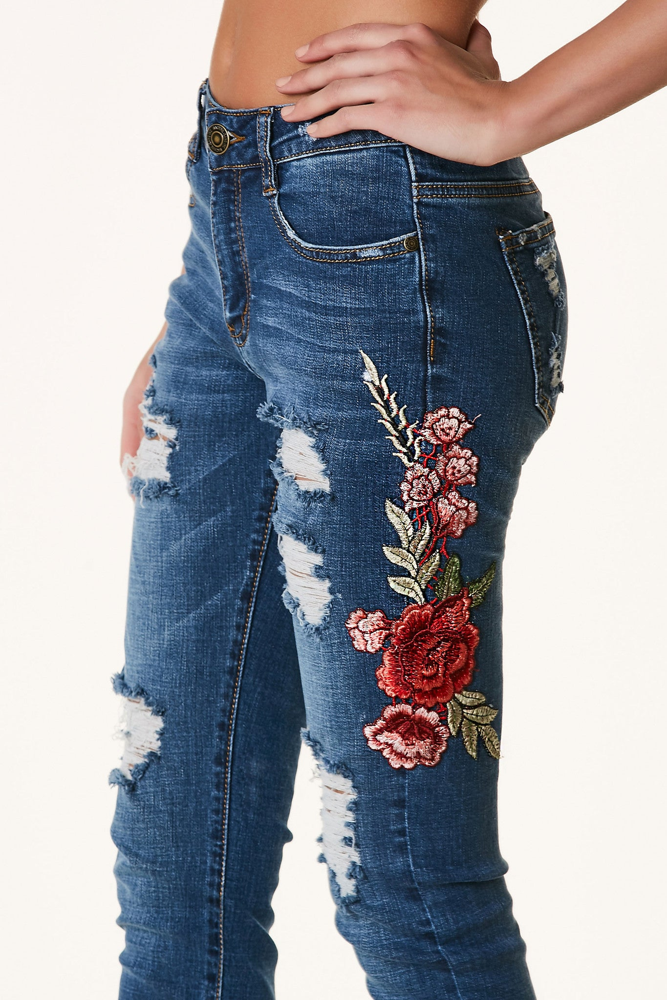 Classic blue mid rise jeans with distressting throughout and intricate floral patch detailing on one side.