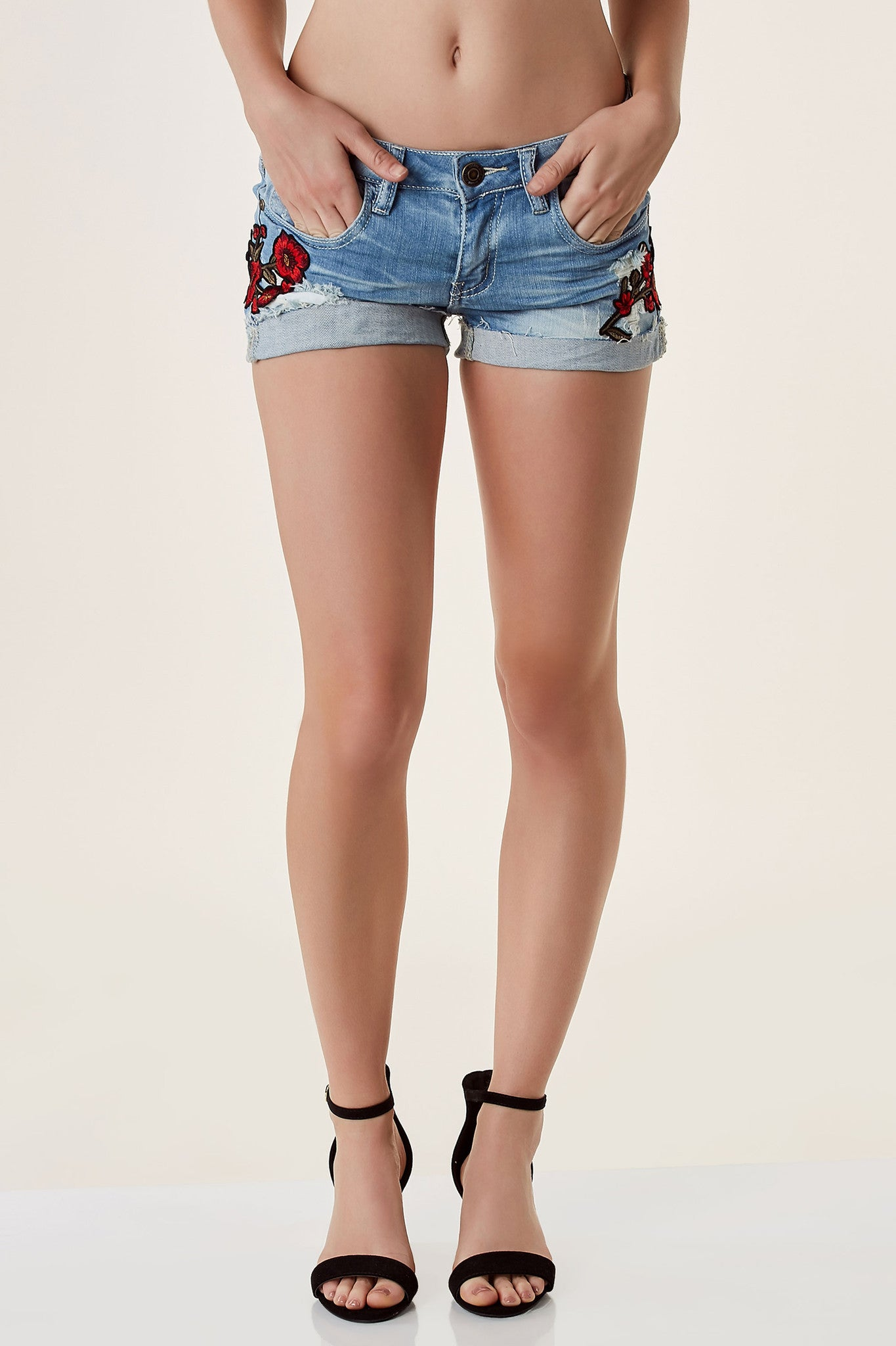Comfortable stretchy pair of low rise shorts with faded detailing and distressing throughout. Colorful floral patches on each side with cuffed hem finish.