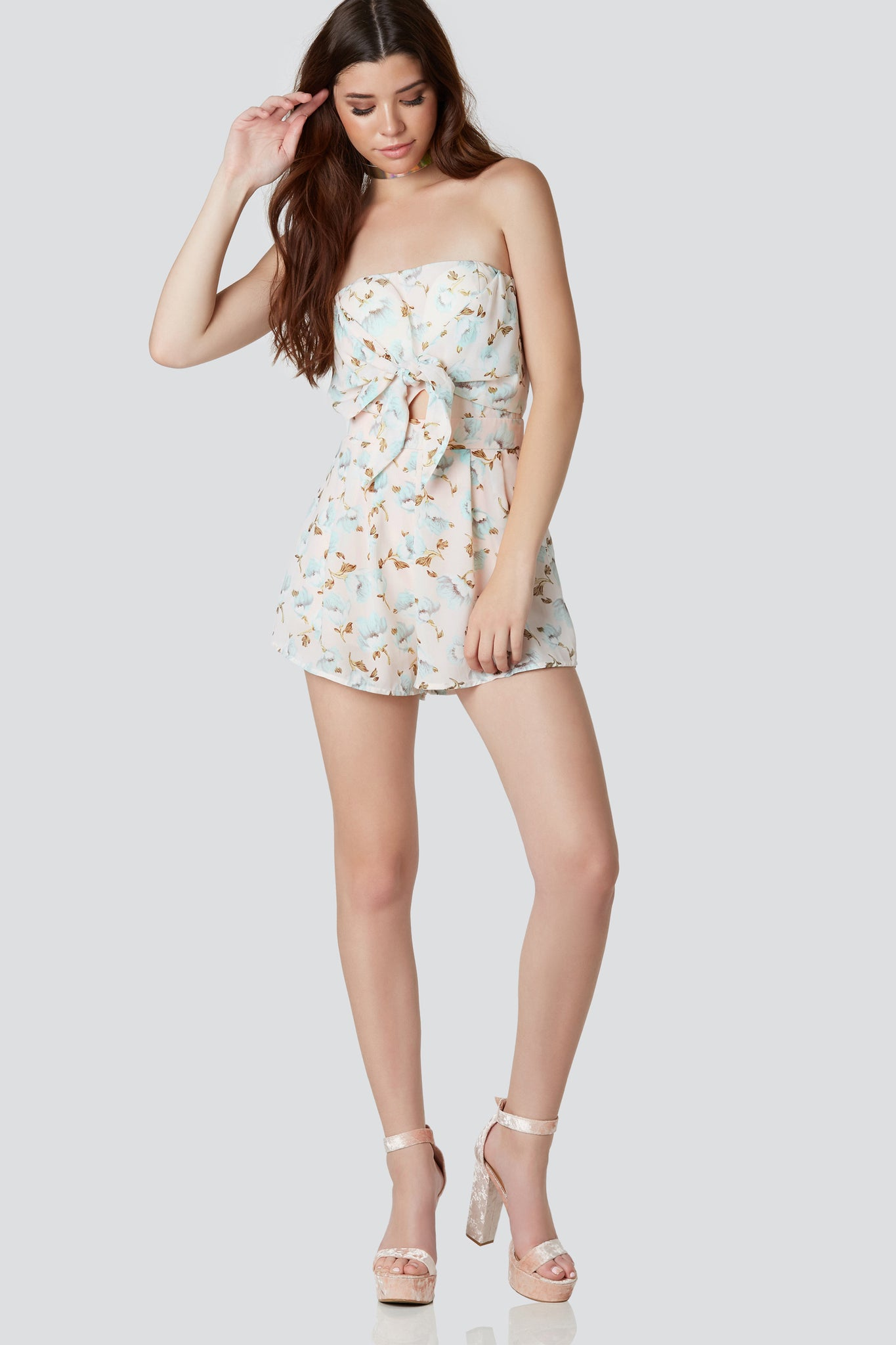 Strapless tube romper with flirty front tie detailing. Floral patterns throughout with small cut out at center and back zip closure.