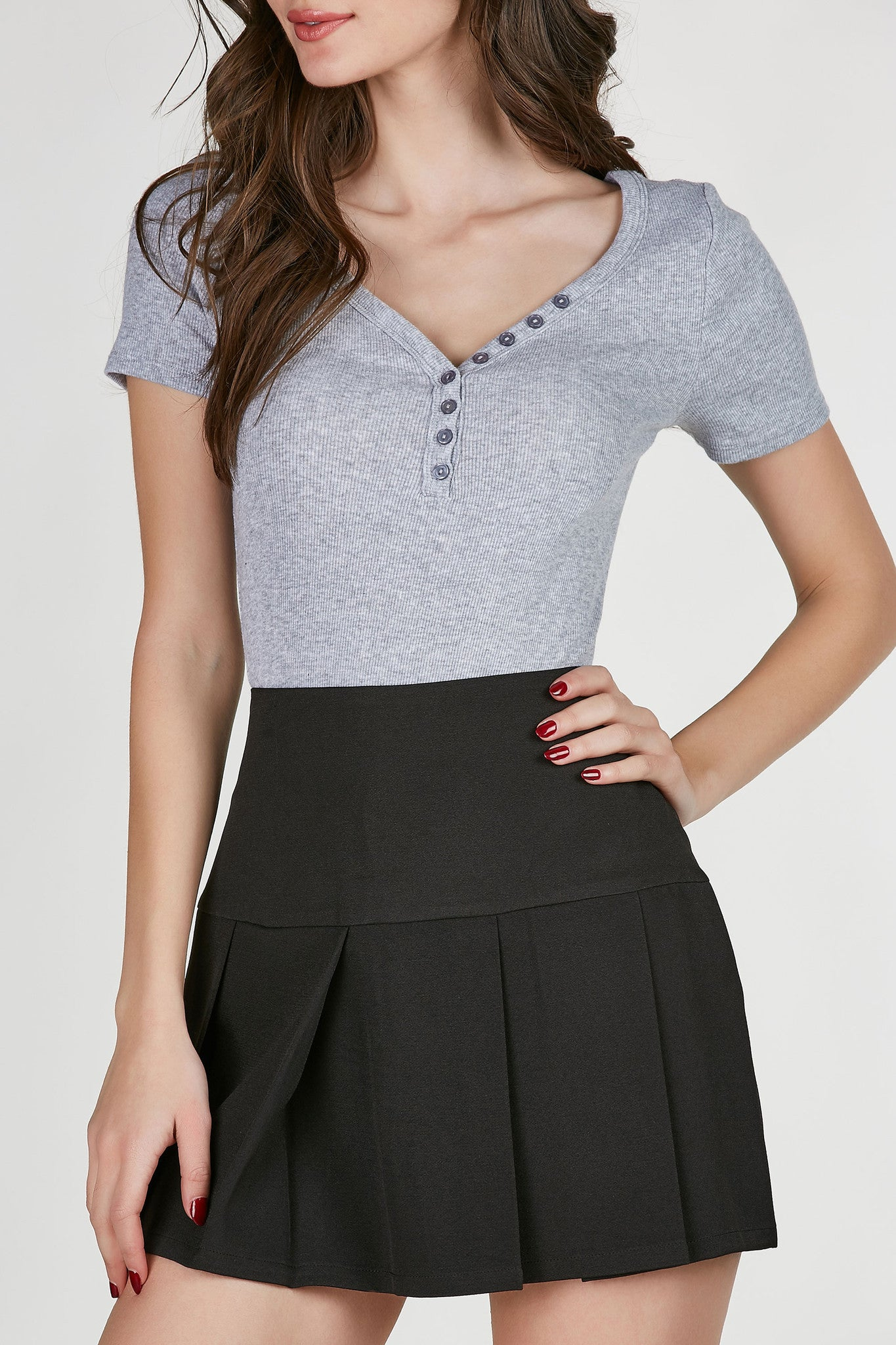 V-neck short sleeve ribbed top with slightly rounded hem. Ribbed throughout with faux buttons for added detail.