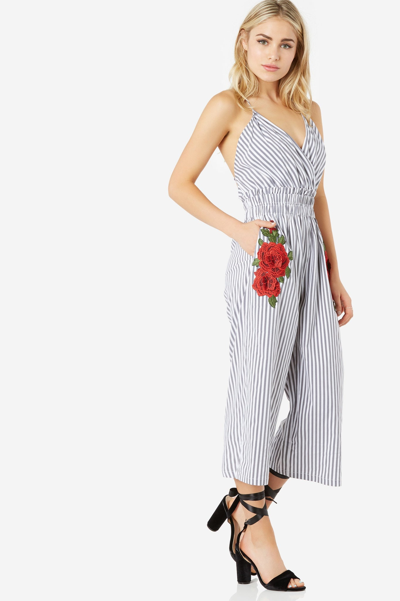 Sleeveless jumpsuit with stripe patterns throughout. Bold floral patches with wide leg fit.