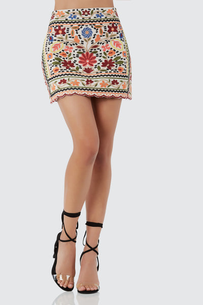Bold mini skirt with colorful embroidery throughout. Back zip closure with scallop hem finish.