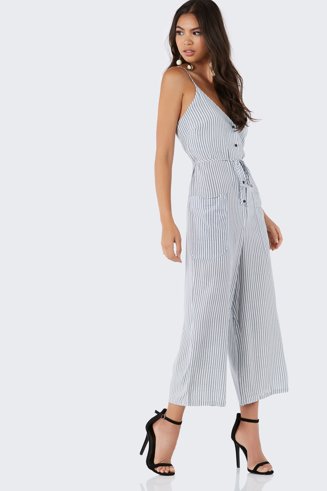 Lightweight sleeveless jumpsuit with stripe patterns throughout. Button front closure with loose fit.