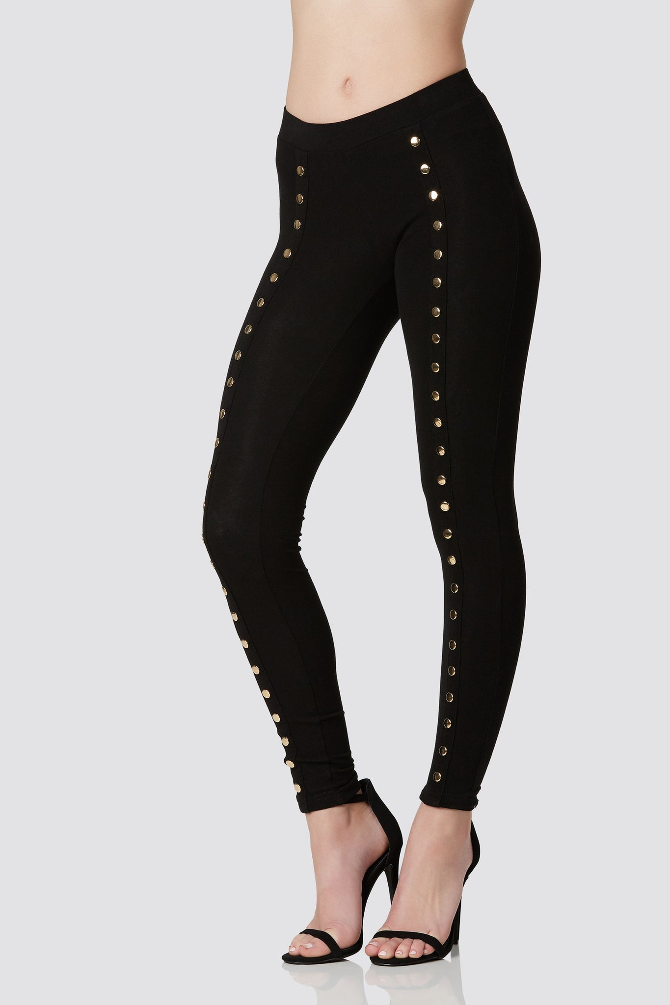 Slim fit basic leggings with trendy faux snap button detailing down each leg. Stretchy material with straight hem finish.