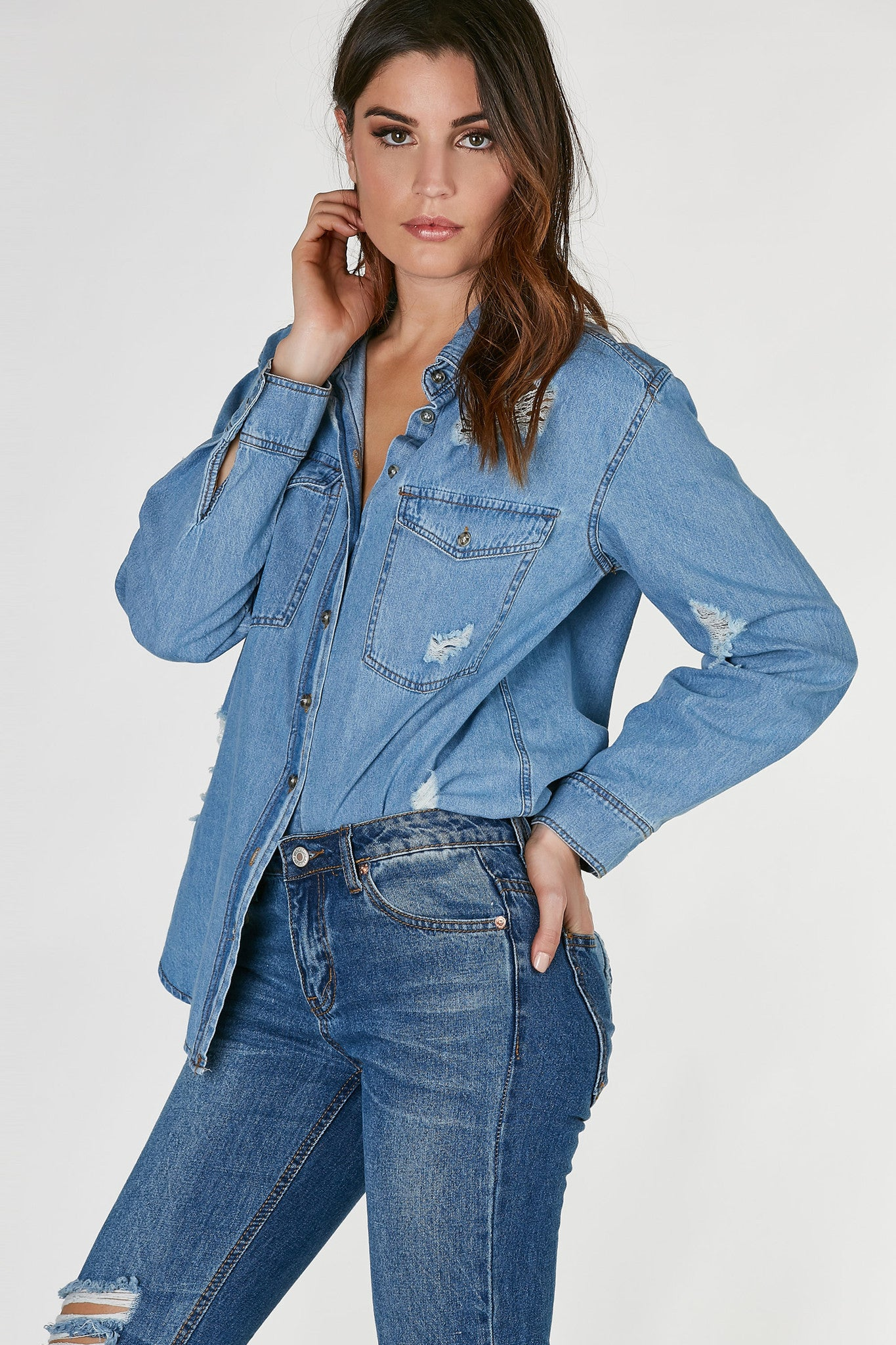 Classic chambray button down with oversized fit and distressing throughout. Rounded, longline hem with slightly longer back.