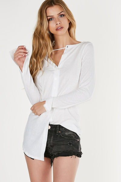 Relaxed fit long sleeve top with laced neckline and button front closure. Soft lightweight material with longline hem.