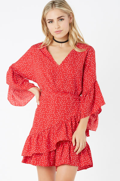Flirty V-neck dress with polka dot print throughout. Ruffle design with wrap front detail.