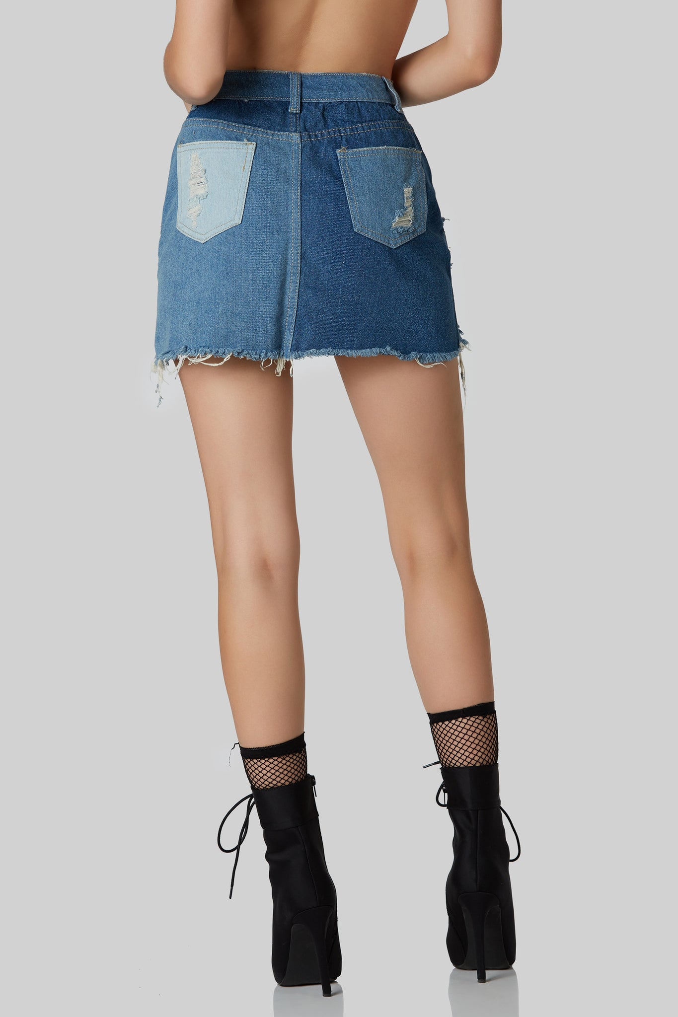 Distressed mid rise denim skirt with color block patched design. Frayed raw hem finish with button and zip closure.