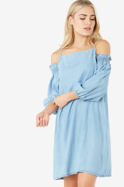Lightweight chambray dress with spaghetti shoulder straps and cold shoulder design. Ruffle trim detailing at sleeves with back zip closure.