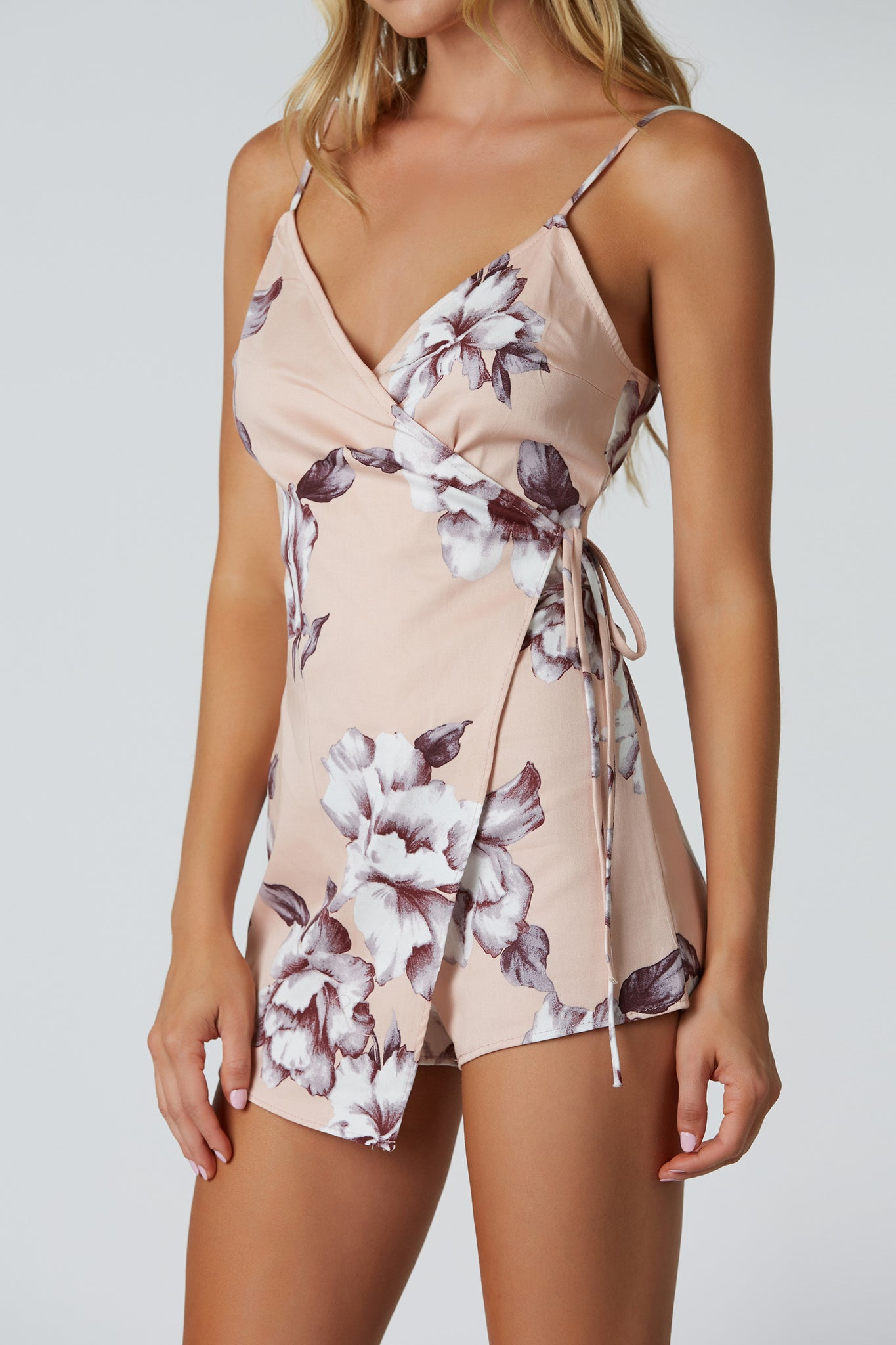 Spaghetti strap printed romper with floral patterns throughout. Stretchy material with back zip closure and chic wrap over front.